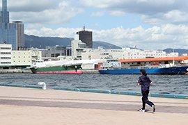 神戸の海を眺めながらランニングする女性イメージ