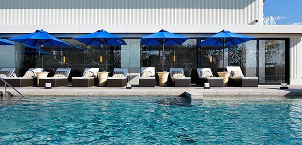 屋外温水プールの青いパラソル風景