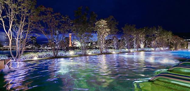 夜のライトアップを反射して光の模様が浮き出た屋外温浴プール