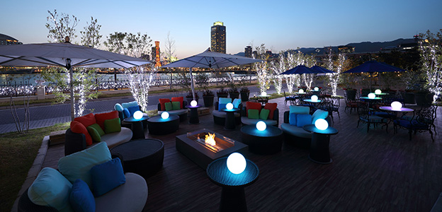 テーブル上のライトが点灯した屋外温水プール 多目的広場