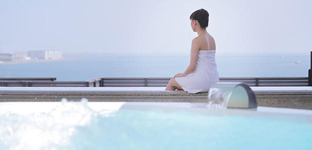 展望露天風呂から神戸港を眺める女性