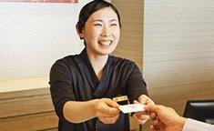 ポイントカードを手渡す神戸みなと温泉 蓮のスタッフ